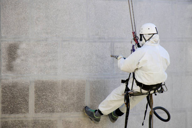 Worker wearing a protective gear cleaning a stone faceade in rope access
