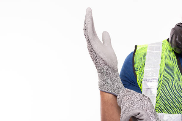Worker wearing construction safety gloves before working. Caucasian contractor or engineer guy preparing for work at worksite by wear safety glove for protect labor hands copy space, isolated on white stock photo