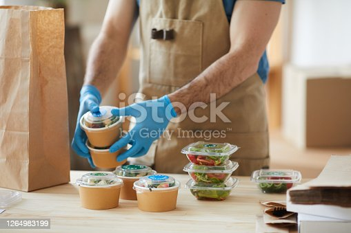 istock Worker Wearing Gloves at Food Delivery Service 1264983199