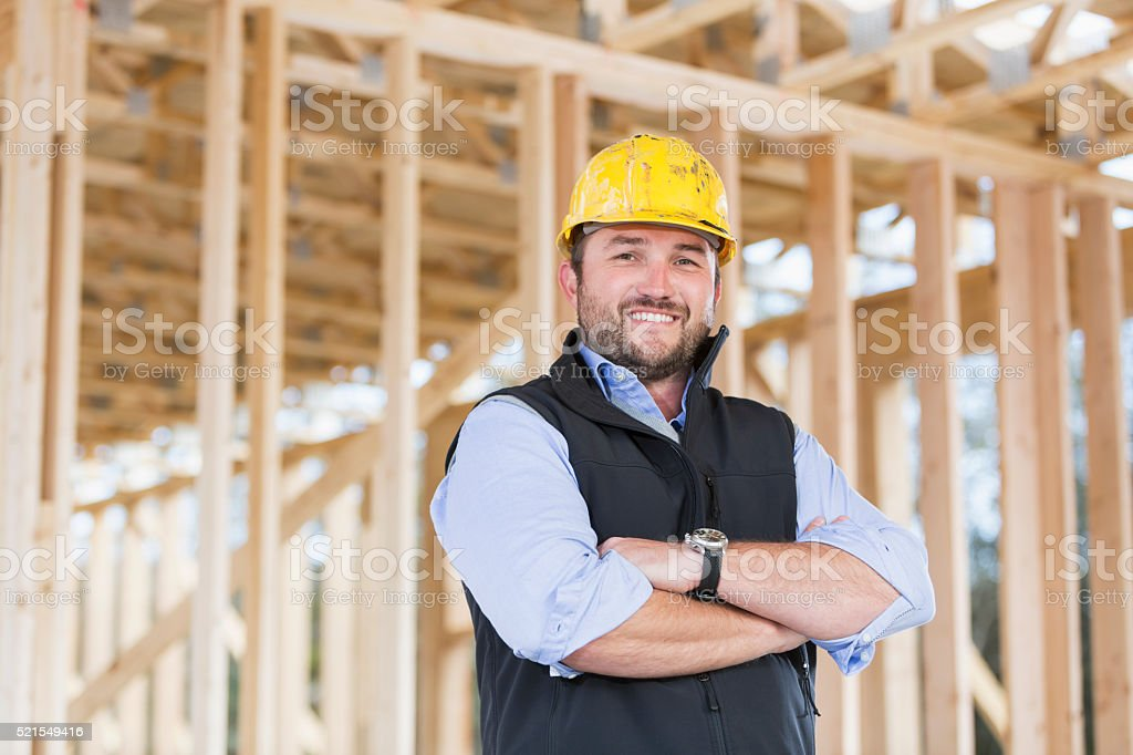Worker wearing hardhat at construction site stock photo