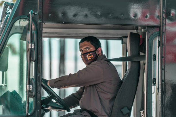 ups worker wearing mask keeps america moving - essential workers stock pictures, royalty-free photos & images