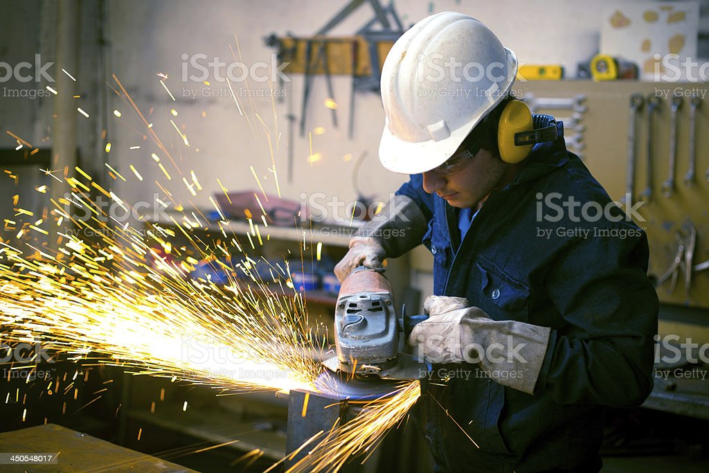 Worker wearing safety gear using grinder with sparks flying stock photo