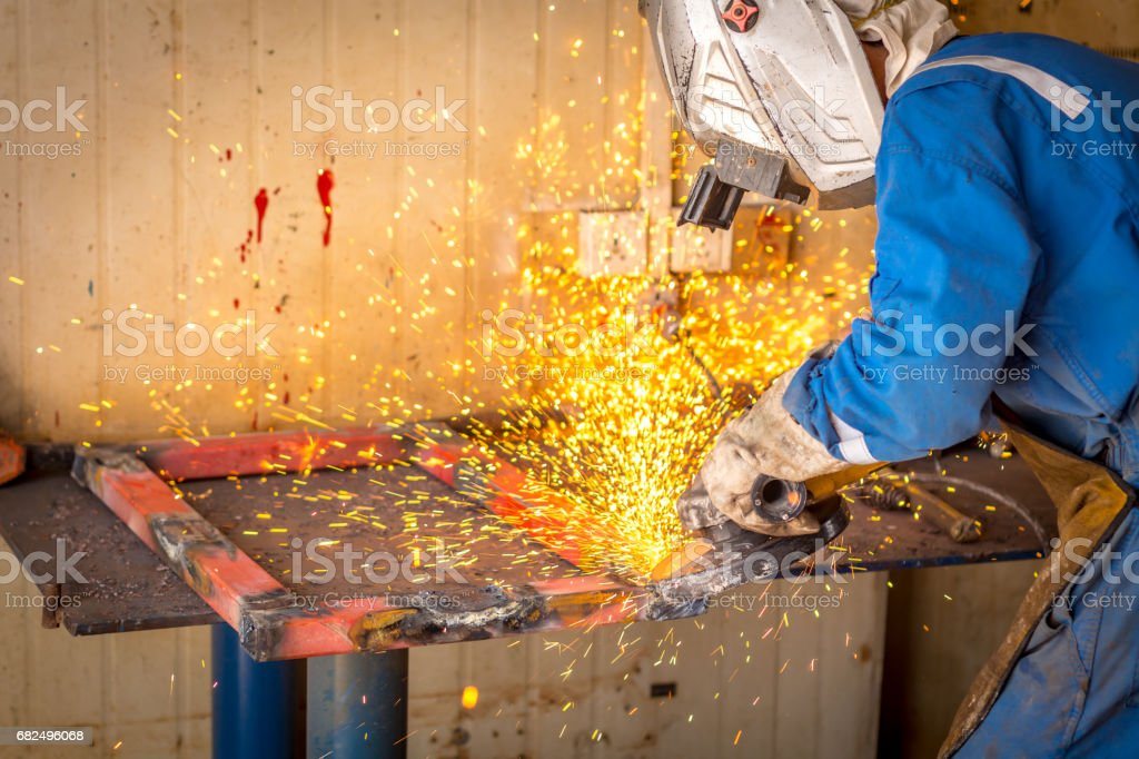 Worker wearing safety gear using grinder with sparks flying royalty-free stock photo