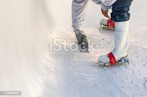 Worker Wearing Spiked Shoes Smoothing Wet Pool Plaster With Trowel.