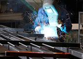 Worker welding an iron part