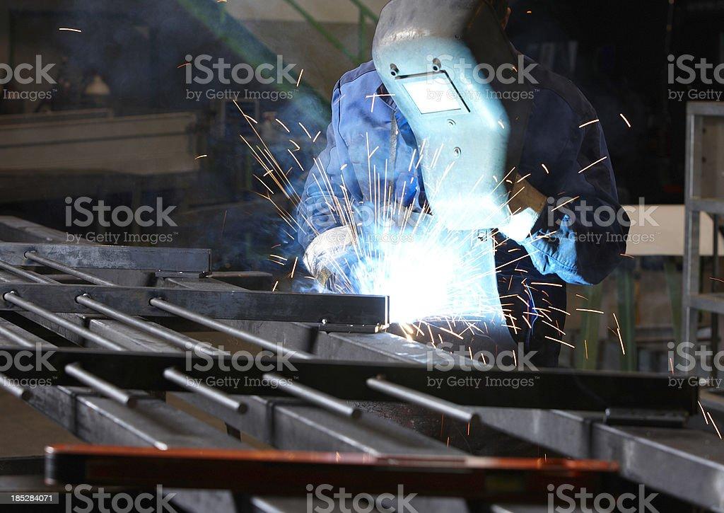 Worker welding an iron part stock photo