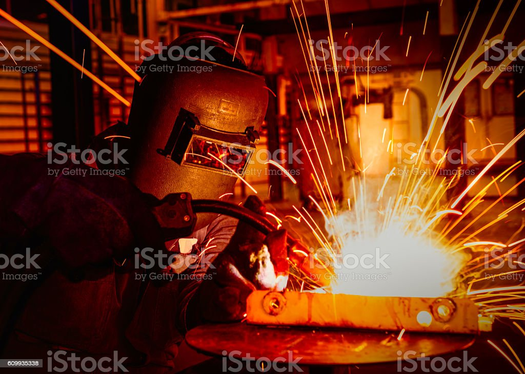 worker welding in factory stock photo