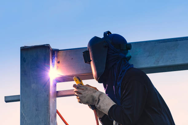 Worker welding parts of stell construction - foto de stock