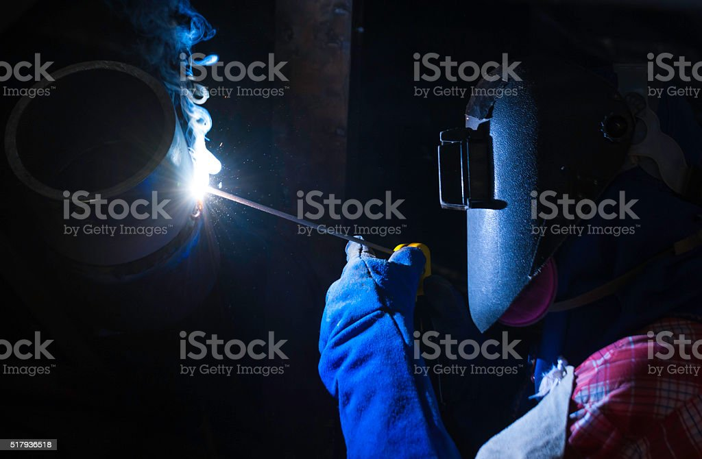 Worker welding pipes using tig welder machine