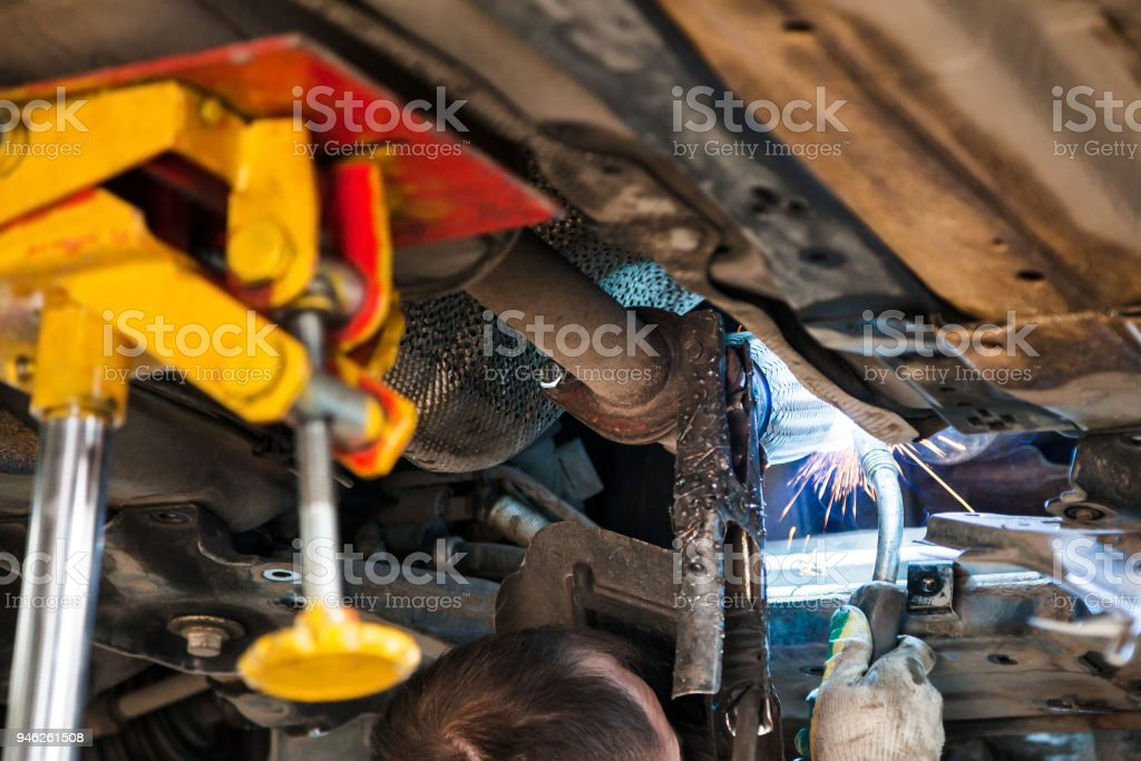 worker welds the silencer on car by argon welding stock photo