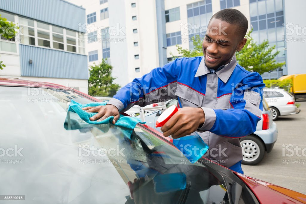 Worker Wiping Car Windshield stock photo