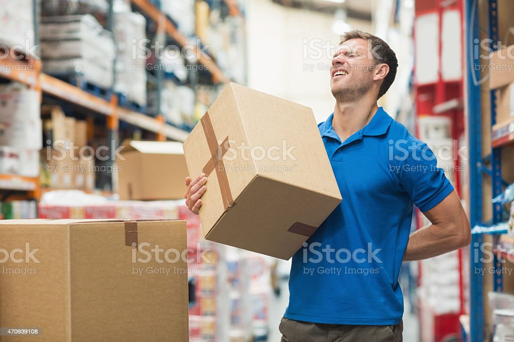 Worker with backache while lifting box in warehouse Side view of worker with backache while lifting box in the warehouse 2015 Stock Photo