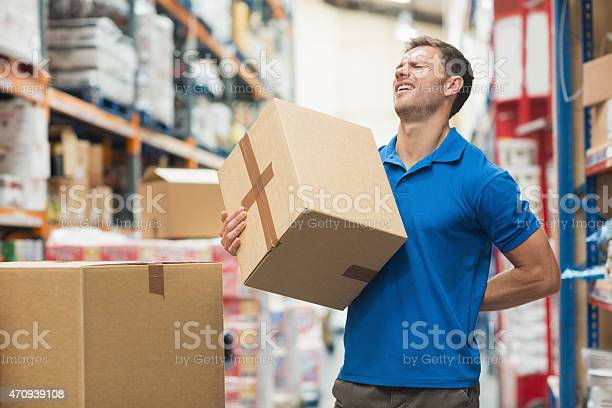 Worker With Backache While Lifting Box In Warehouse Stock Photo - Download Image Now