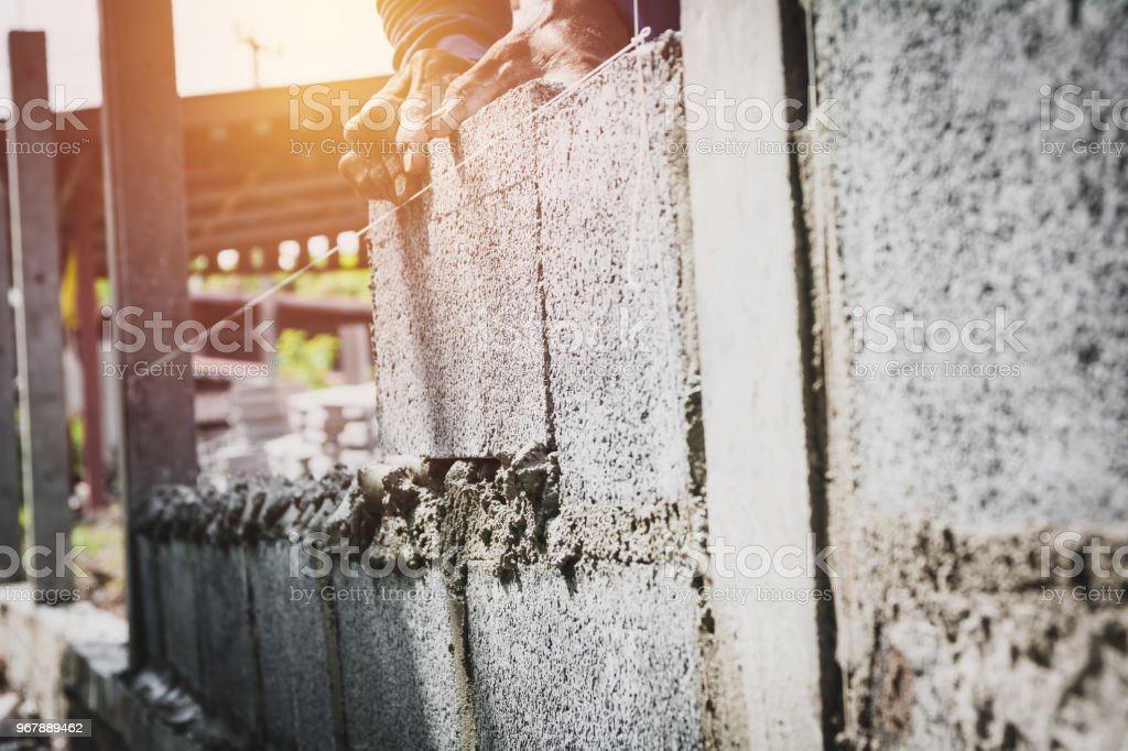Worker with block concrete cement mortar wall at construction site. stock photo
