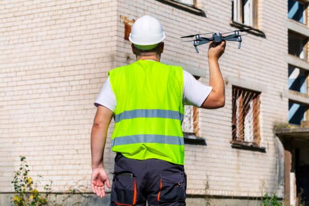 arbeiter mit drohne vor der hand starten - flugdrohne stock-fotos und bilder
