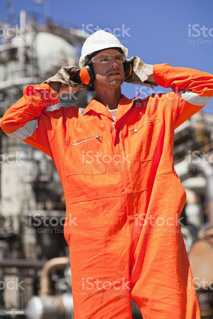 Worker with earphones at oil refinery stock photo