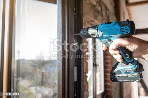 966792200 istock photo worker with electric screwdriver adjusts the window 1209468890