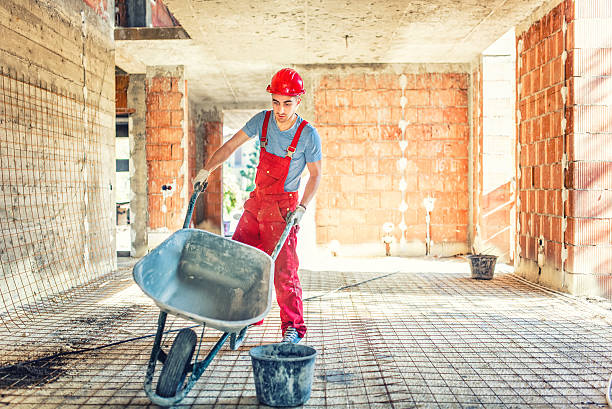 worker with empty wheelbarrow on construction site - kruiwagen stockfoto's en -beelden