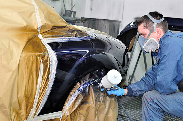 a worker with facemask applying a new coat of car paint - auto body repair stock photos and pictures