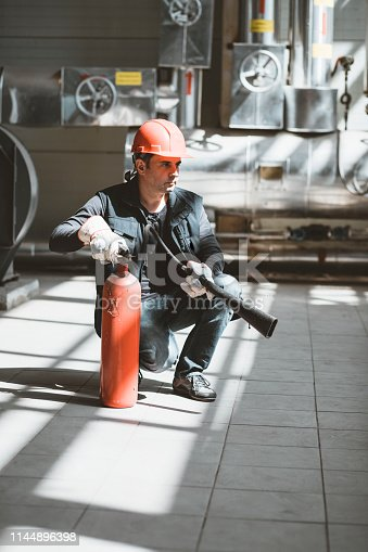 View of a Heating Technician with Protective Helmet who is Working in the Heating Plant and Holding a Fire Extinguisher. Mechanical Engineer is in Factory Surrounded by Industrial Equipment.