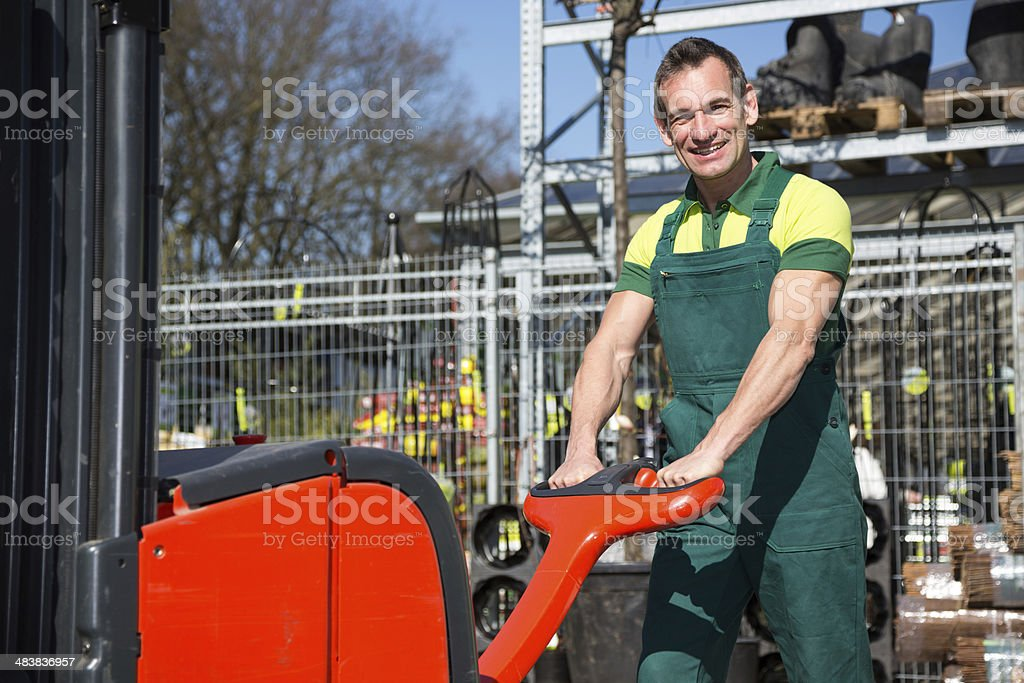 Worker with forklift in warehouse or storehouse stock photo