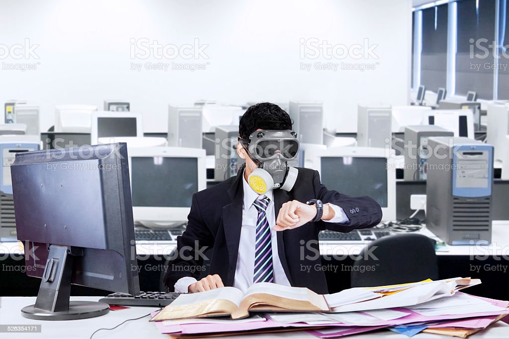 Worker with gas mask in office stock photo