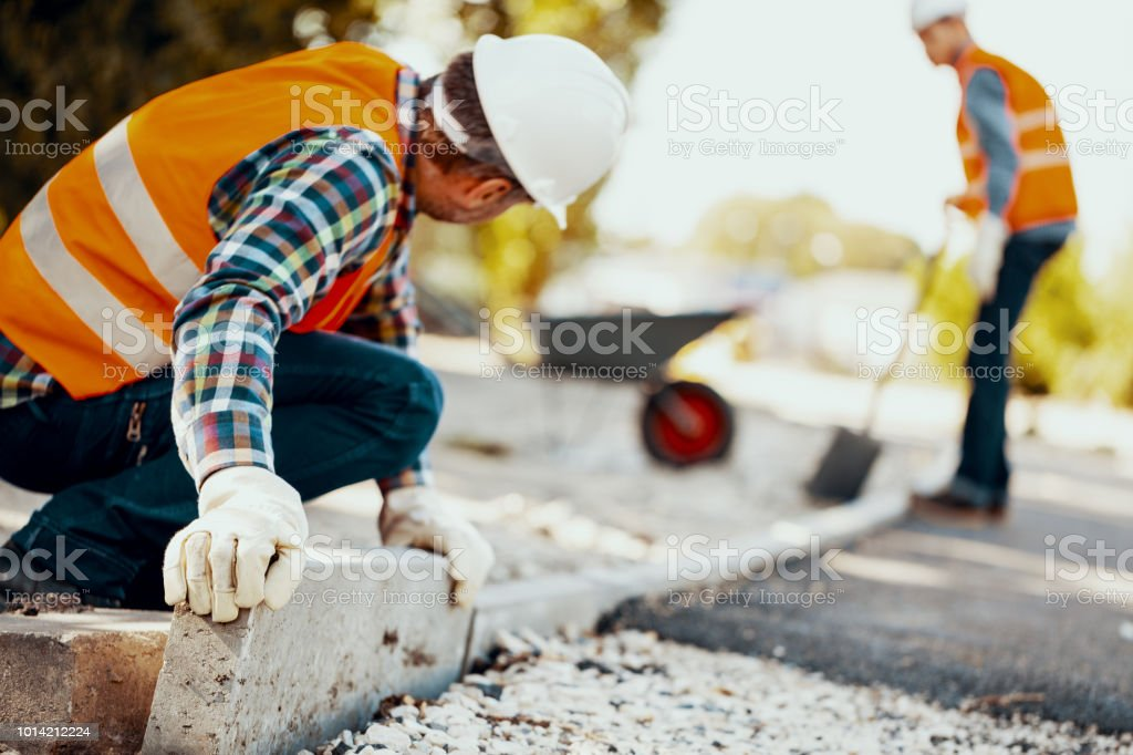 Worker with gloves and in helmet arranging curbs on the street stock photo