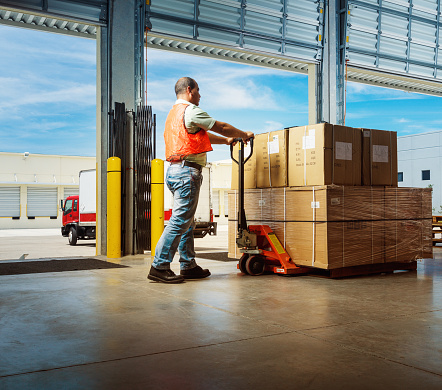 worker pushing an hydraulic hand pallet truck on a warehouse