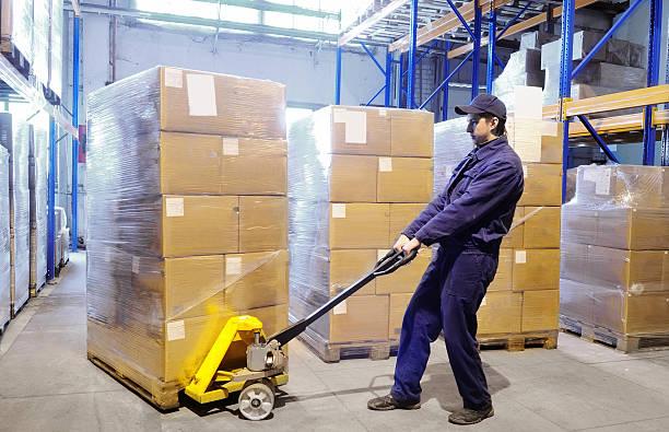 Main Travailleur avec Chariot de manutention des palettes stacker au warehouse - Photo