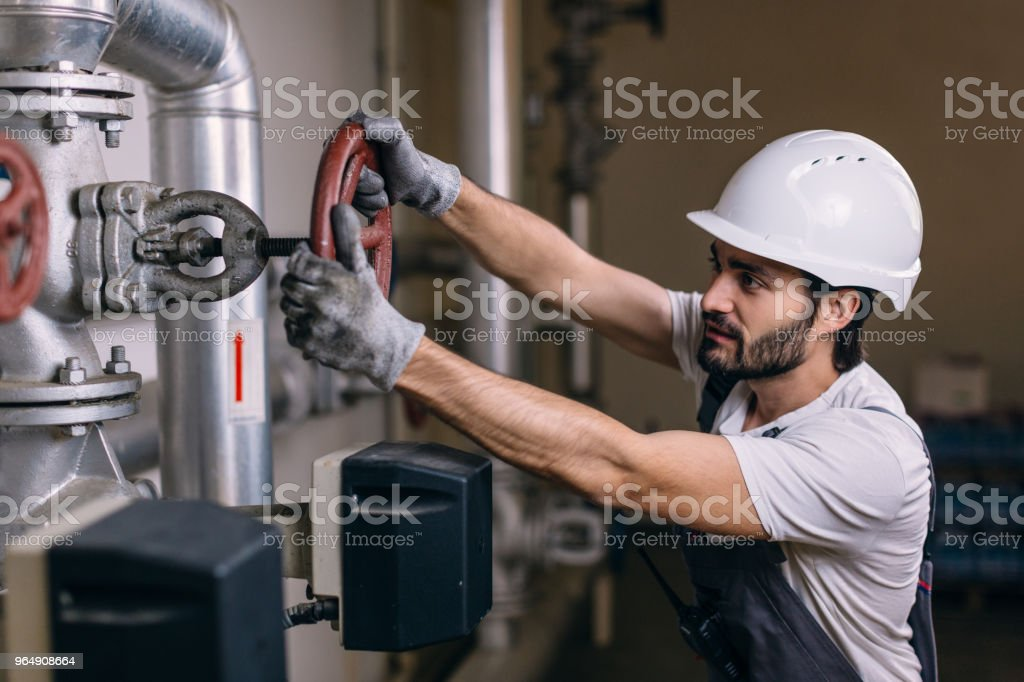 Worker with helmet in front of pipes with valves royalty-free stock photo