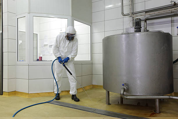 worker  with high pressure washer, cleaning floor in plant stock photo
