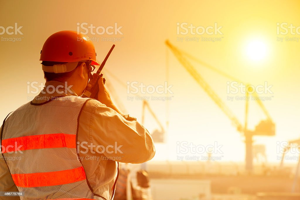 worker with large crane site and sunset background stock photo