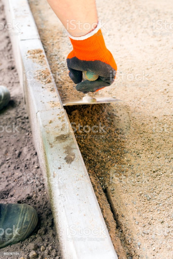 Worker with orange glove uses paving trowel. stock photo