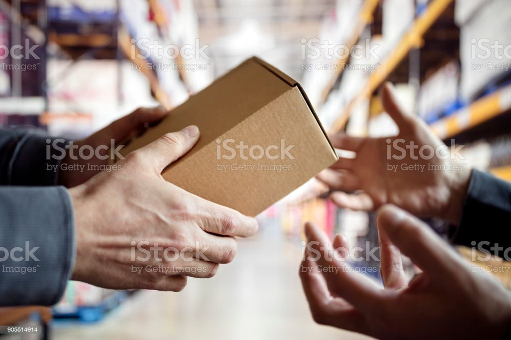 Worker with package in a distribution warehouse stock photo