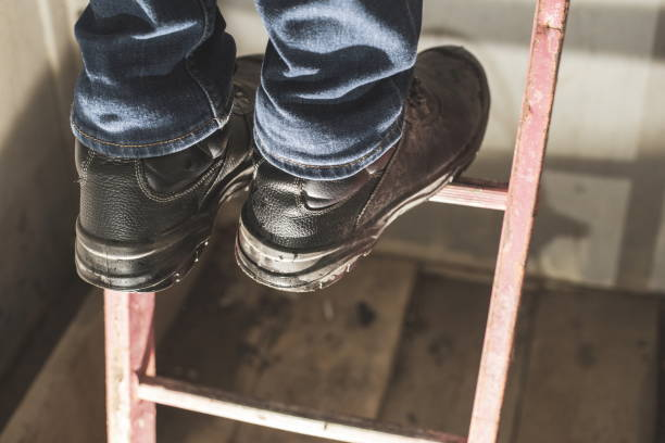 Worker with Personal Protective Equipment. construction worker training at high place. Engineer standing on the ladder. Safety boots on ladder. Protection for construction workers. Architects safety. Focus on boots. warm filter stock photo