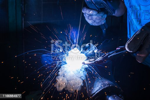 Worker with protective gloves welding metal part in workshop