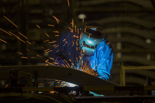 worker with protective mask is welding metal in factory worker with protective mask is welding metal in factory naval base stock pictures, royalty-free photos & images
