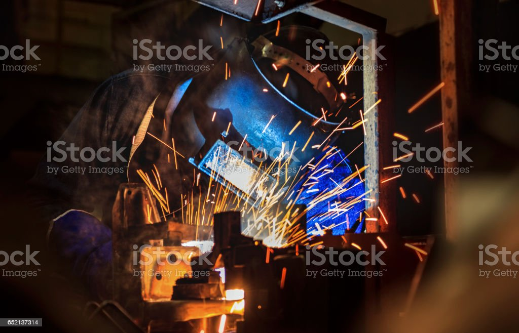 worker with protective mask welding in factory stock photo
