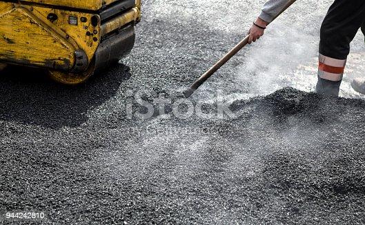 A roller compacting asphalt on a road