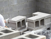 Worker With Safety Gloves Stacking Concrete Blocks