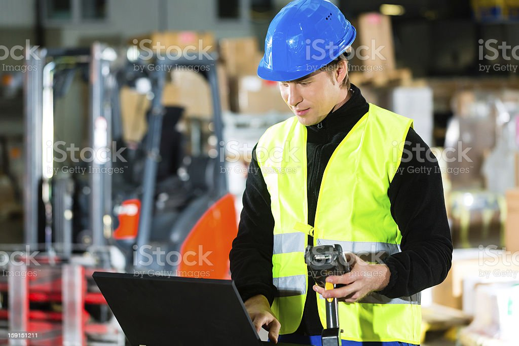 Worker with scanner and laptop at forwarding stock photo