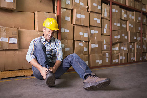 Worker with sprained ankle on floor in warehouse Male worker sitting with sprained ankle on the floor in warehouse misfortune stock pictures, royalty-free photos & images