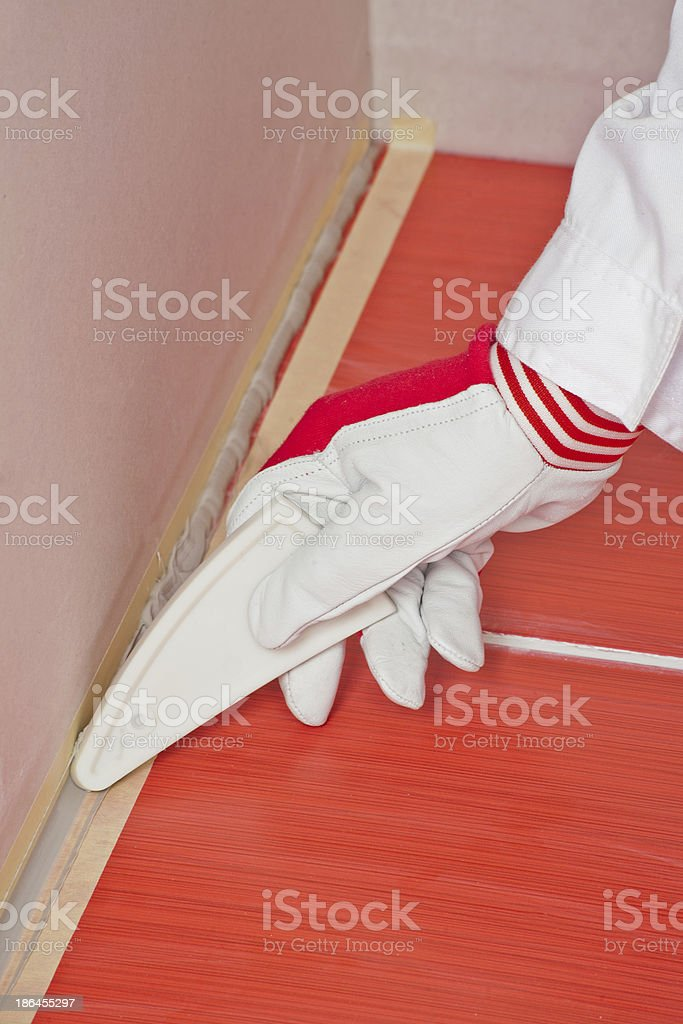 worker with tool smooth silicone sealant on corner tiles royalty-free stock photo