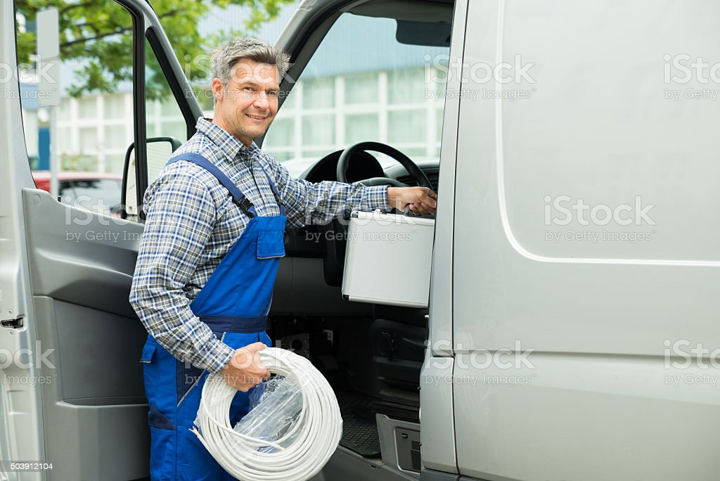 Worker With Toolbox And Cable Entering In Van stock photo