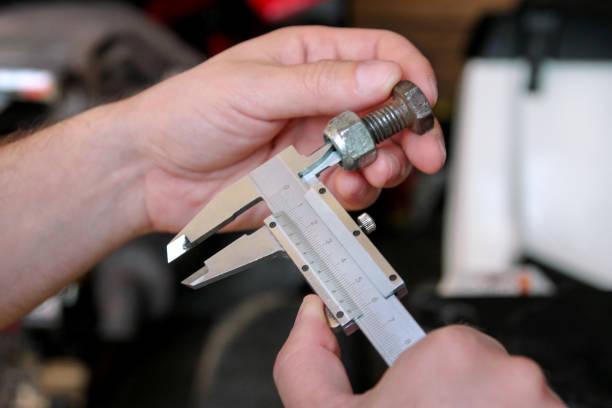 Trabalhador com as ferramentas nas mãos. O mecânico está verificando e medindo o tamanho do parafuso com paquímetro do aço inoxidável na oficina dos automechanics, garagem do carro. Mãos do mecânico que prende o parafuso de aço usando o compasso d - foto de acervo