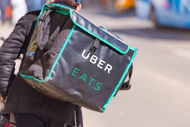 arbeiter mit uber isst fahrrad und eine tasche in einer straße von moskau - kinder die schnell arbeiten stock-fotos und bilder