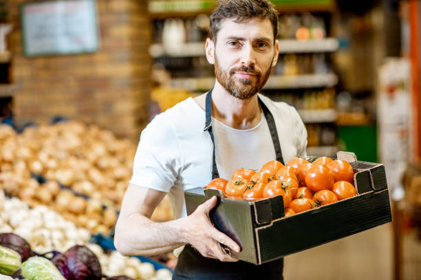 Worker with vegetables in the supermarket Portrait of a handsome shop worker or farmer holding box with fresh tomatoes in the vegetable department in the supermarket homegrown produce stock pictures, royalty-free photos & images