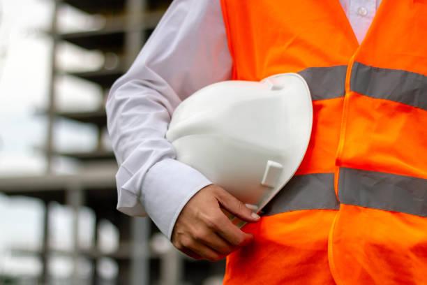 pracownik z białym hełmem bezpieczeństwa i pomarańczową kamizelką. koncepcja pracowników budownictwa i przemysłu - kask ochronny odzież ochronna zdjęcia i obrazy z banku zdjęć
