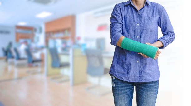 worker woman accident on arm with green arm cast on blurred business office working space background stock photo