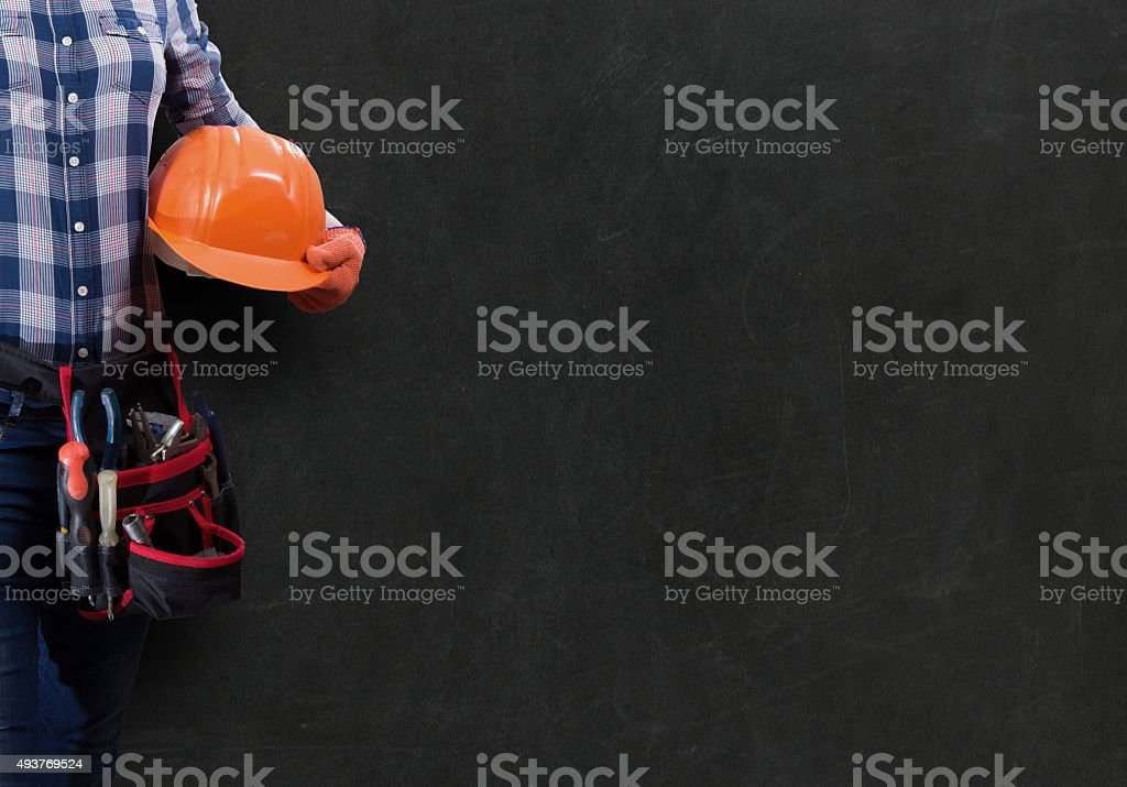 Worker woman with toolbelt and helmet against dark background stock photo